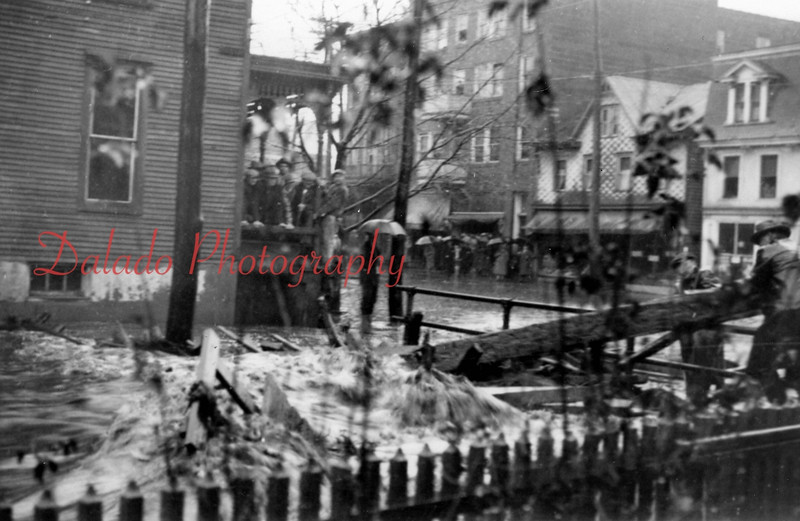 Spruce Street during a flood. The building with the A-framed roof is now the location of Mr. Pizza.