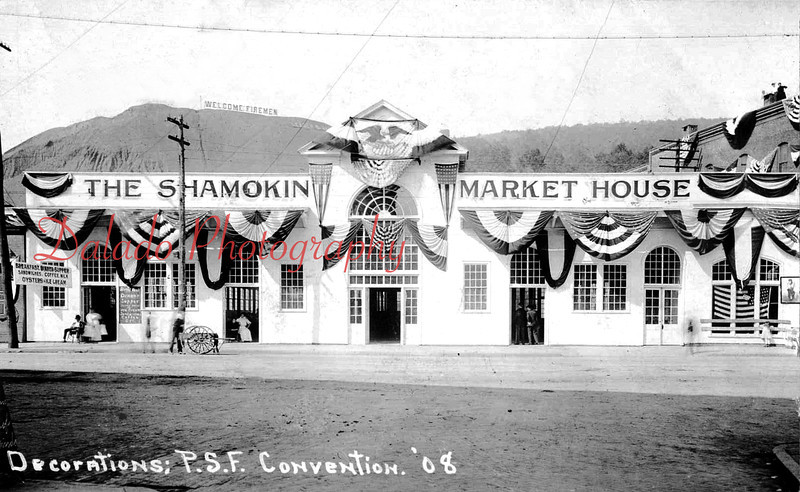 """(1908) The Shamokin Market House- Decorated for the P.S.F. Convention. On the Glen Burn Bank there is a large sign that reads, """"Welcome Firemen."""" The sign at left reads, """"Breakfast, Dinner, Supper, Sandwiches, Coffee, Milk, Oysters + Ice Cream."""""""