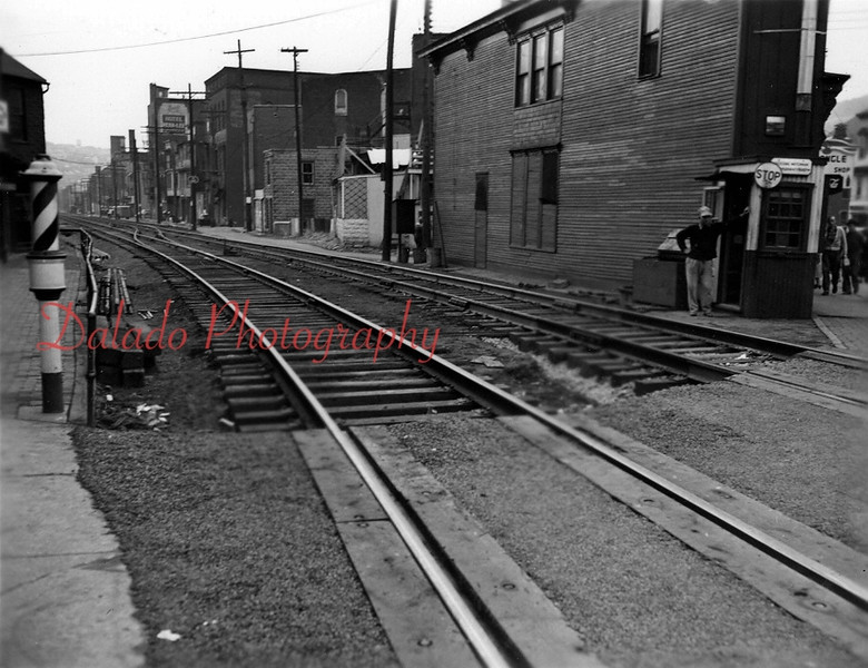"The railroad crossing at Station Row, left, and the ""Times Square"" building, right, at Independence Street. The Times Square building now houses Chillers. Water Street (background) was expanded in 1964 when Reading Railroad Company abandoned the line at right."