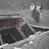 (May 1959) Mary Bulka and Irene Zanella and children point to an open mine shaft that is near their homes in Dooleyville.