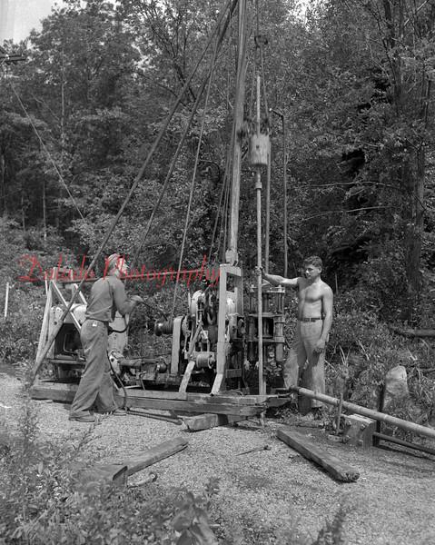 (1954) Men drilling.