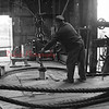 (July 1956) Driller Harold Burdic works at the Farmer's Well No. 1 near Numidia. The derrick has been pounding a hole into the earth for the last six months. Hole has to reach 4,590 feet in order to reach the Oriskany sand.
