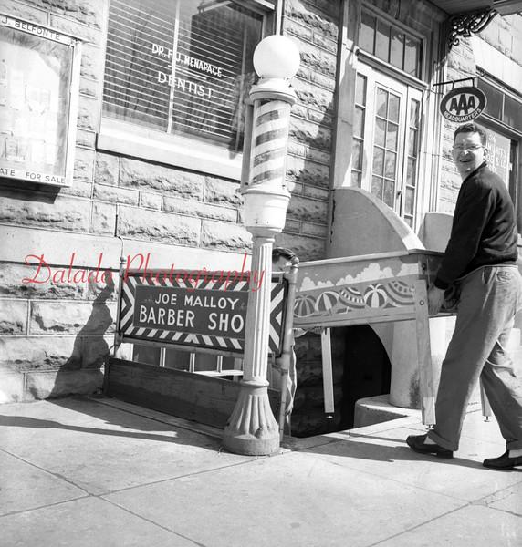 (03.29.1956) Pinball machine being takin out of Joe Mallory Barber Shop along Third Street in Mount Carmel.