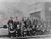 """(05.01.1931) Shown are men of the Reading Railroad Yard, Shamokin, at the engine house on May 1, 1931. The engine house was built between 1927 and 1929. """"Engine House Gang."""" Pictured are, standing, from left, Harry Adams (Carpenter), Harry Yocum (Hostlers Helper), George Wendell (Hostler), Alley Hummel (Stationary Boilerman), Milt Troutman (Machinist), Clayton Deppen (Storehouse), Harry Persing (Blacksmith Helper), Bill Esslick (Boiler Washer), Ben Wraggs (Boiler Marker) and John Murphy (Machinist); seated, John Coleman (Storekeerper), Bob Unger (Airbrake Inspector), Frank Klemick (Fire Cleaner), John Hower (Blacksmith), Elwood Spotts (Boilermakers Helper), Edward Yocum (Laborer), Reynold Perry (Machinist), Frank Johns (Boilermakers Helper) and Bob Lindermuth (Laborer)."""