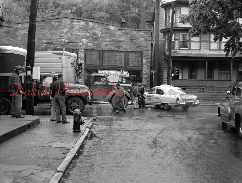 (May 1954) A taxi and tractor-trailer collided at Sunbury and Market streets. Showing giving the details to Patrolman Charles Marinick is Mr. Henderson, driver of the truck, and George Dindorf, taxi driver.
