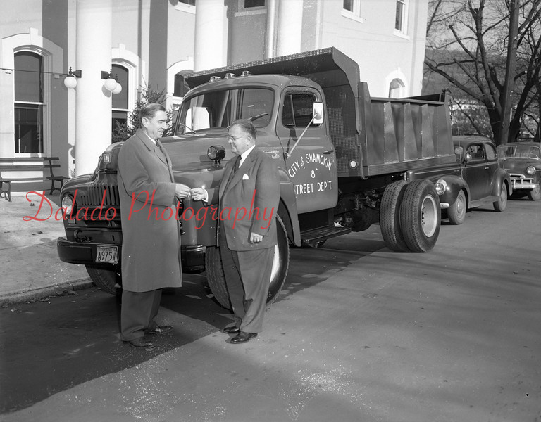 (12.13.1951) Shamokin Mayor Thomas Landy accepts the keys to a new International delivered by John Belsky, of Tharptown, on Dec. 13, 1951.