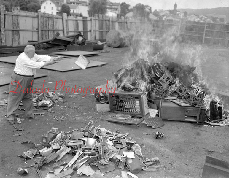 (July 1954) Ray D. Marshall, county detective, throws more fuel on the fire as 173 punch boards and 34 slot machines are destroyed. The devises were confiscated in six months by local police.