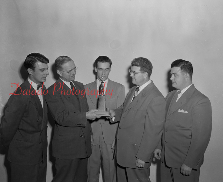 (04.12.51) Presbyterian Church receives championship trophy. Pictured are Rev. Roy Miller, pastor, receiving the basketball championship trophy from Ward Lichtel, representing First E.U.B., winners of the trophy last year. Others in the picture are L. Buffington, Dave Milbrand and Jim Scott.