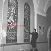 (02.02.56) Looking over the stained glass windows installed in St. Anthony's, Ranshaw, is Rev. Thomas Gralinski, assistant pastor of the church. The windows represent five mysteries of the Rosary.