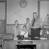 "(Jan. 1958) Guest police chief Joseph Homanoski, seated, takes over the city hall desk from Chief George Haddock. Guest safety commissioner, Kenneth Noll, and solicitor, Daniel Ciesluk, helped the ""chief for the day."" All boys are members of the St. Stanislaus Seven Star Civics club."