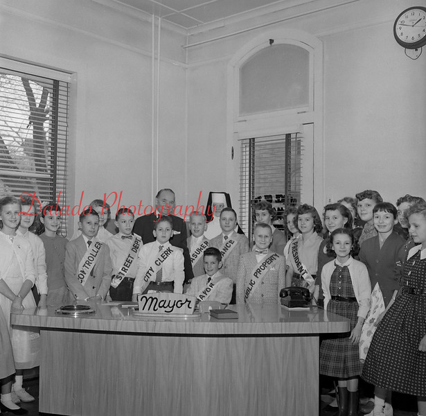 "(Jan. 1958) Mayor Lester Weller makes welcome to city hall seventh-graders from St. Stanislaus Seven Star Civics Club. Their teacher, Sister Mary Emeline, arranged their visit as part of a project entitled ""The Citizen and His Government."" Guest Mayor was Gary Dombroski. Controller. Alex Kaschock; street department, Robert Porter; city clerk, Gerald Slaby; treasurer, Henry Zielanis; finance, Robert Sock; public property, Kenneth Strunk; and Louise Pogozelski, president of the club."