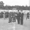 (1959) During a Midget League football game at Kulpmont Stadium, American Legion Post Commander Stephen Watral Jr. presents the organization's Better Citizenship and Americanism plaque to Martin Zarkoski, Explorer president,  in recognition of the work done by the Scout Troop at the stadium. Looking on are George Ladika, Explorer adviser, and Joseph Katona, Legion adjutant.