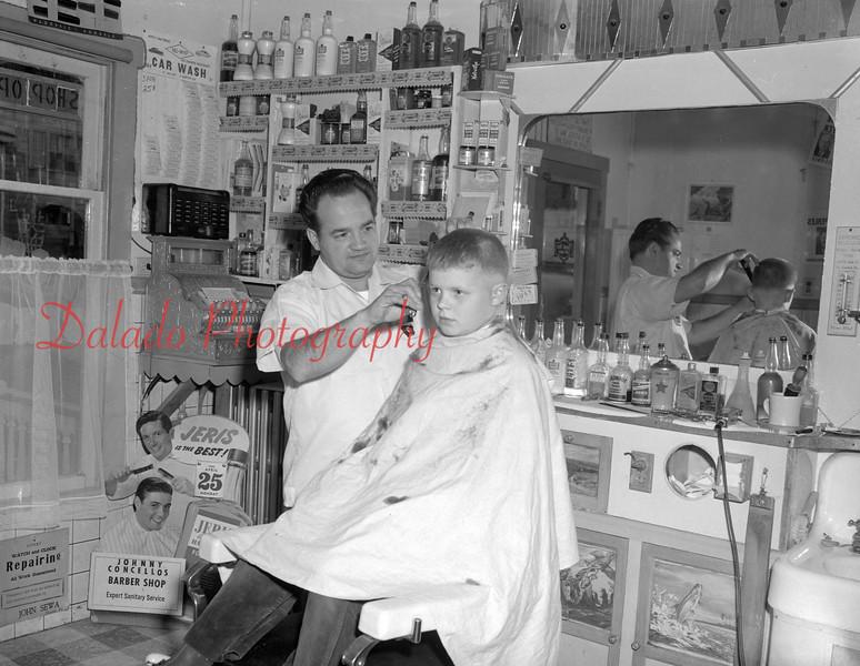 (April 1953) Johnny Concellos Barber Shop. (Unknown location)