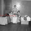 (07.15.54) Sorting clothing are Clarence Weline, seated, from left, Judy Werner and Barbara Werline for shipment to new Windsor, Maryland, where it will be cleaned before being shipped overseas.