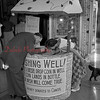"(July 1954) Trying her luck at winning free tickets to the CinemaScope production of ""Three Coins in the Fountain,"" which is being unreeled at the Vickey is Shirley Delbaugh, who leans over the wishing well located at the trance to the theatre in an attempt to drop a coin in a bottle. All money collected will be donated to the American Cancer Society."