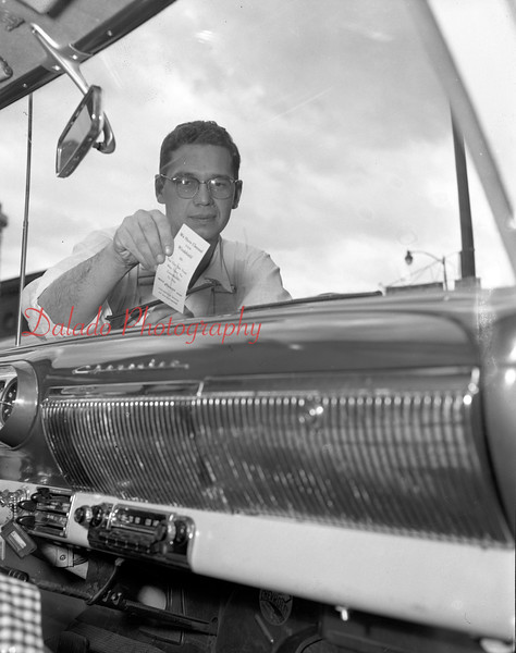 (05.24.56) Fritz Reed attaching a card to a windshield to remind motorists to give to the Caner Crusade.