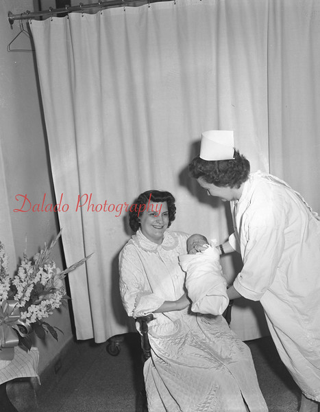 (03.01.56) Mrs. Roland Ferentz with her son, Roland Mark, born Feb. 21, 1956, 10:44 a.m.. First boy in the family. Three sisters: Mary Ann, 6, Margaret Louise, 3, and Deborah, 2. Mrs. Jean Rosinski is handing the baby to his mother.