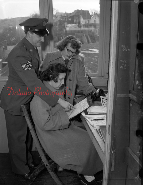 (March 1954) Volunteers in the Ground Observation Corps are shown. Misses Rose Marie Senoskie and Schmidt, students at Coal Township, are instructed by Sgt. S.G. Smeltzer.