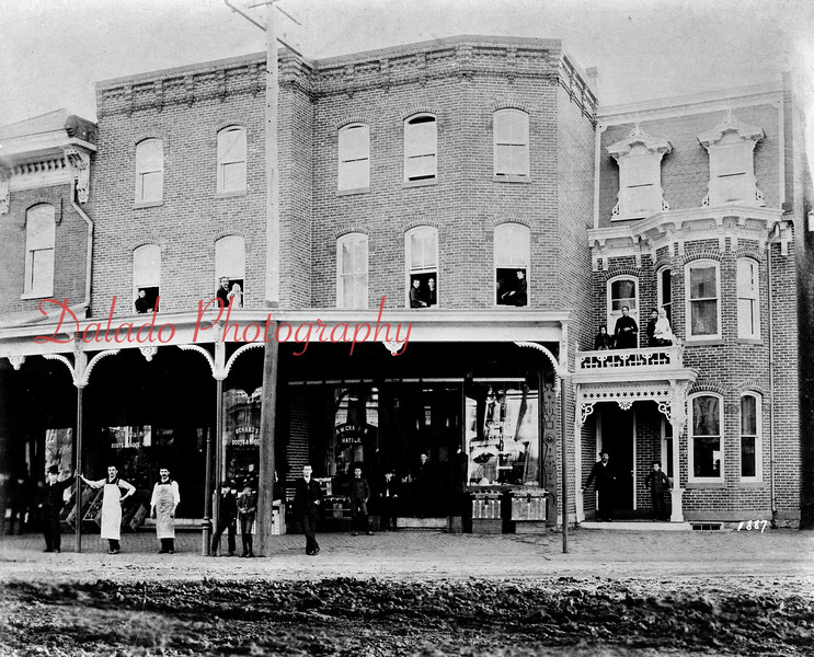 (1887) Buildings near the southwest corner of Independence and Liberty streets. Now the location of OIP, this is the old location of Schabo's Show Store, A.W. Graeber's Clothing Store, Sam Dluge's Clothing Store and The Bootery Store. Cornelius Raker, owner of the building for many years, (standing on porch at right) was known for his photography work  until he retired  from the business in 1890.