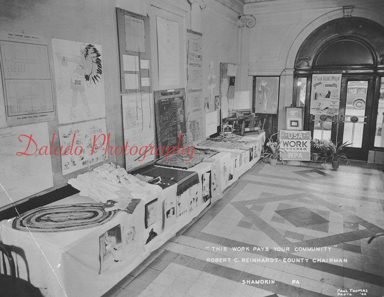 """(1940) Weaving display inside the American Not sure what this is about, but the material seems to show the products that came out of Shamokin at that time. The text stamped on the bottom-left of the photo reads, """"'This work pays your community'  Robert C. Reinhardt- County Chairman."""""""