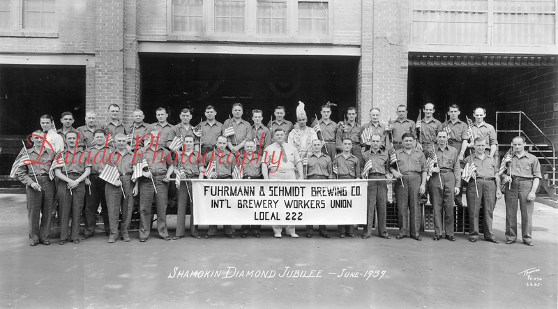 """(06.1939) Members of the Fuhrmann and Schmidt Brewing Company International Brewery Workers Union Local 222 stand in front of the firm's main offices at Commerce and Washington streets in Shamokin in June of 1939. Included in the photo is Ike Zielinskie, front row, fifth from left; Frank Omlor, master brewmaster, ninth from left; and Jerome Zielinskie, twelve from left; back, """"Nibs"""" and Bob Appel, second and third from right; and Patrick Kearins III, back row far right."""