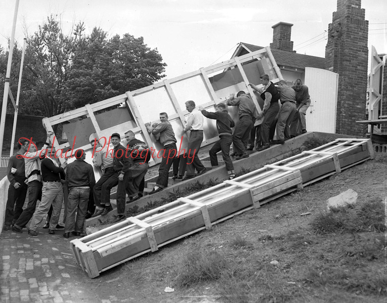 (1955) Coal Township High School football players help move a new scoreboard.