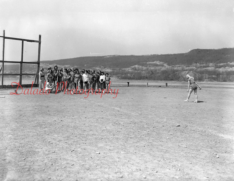 """(April 1954) Kulpmont High School girls brave high temperatures to engage in a game of softball as part of physical education period, under the direction of Florence Gdaniec. The """"umpire"""" is Marion Horne, catching is Kitty Landis, batting is Theresa White."""