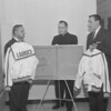 (Dec. 1959) On behalf of the members of Our Lady of Lourdes Booster Association, Leon Korbich, president of the group, presents the school's athletic department with warmup jackets and pants for the Red Raiders. Accepting the uniforms is Martin Benkovic, varsity coach, right, while Rev. Thomas Leitch, principal, watched the presentation from behind a new magnetic diagram board.