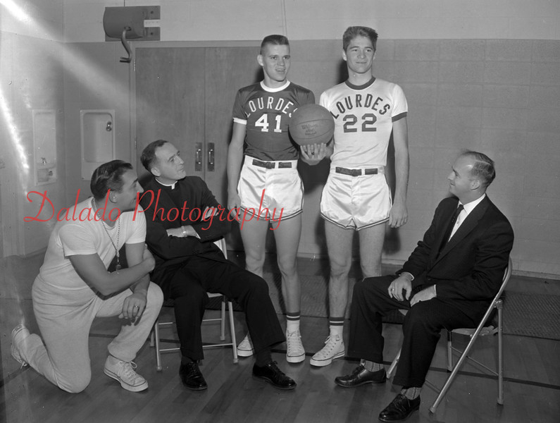 (Nov. 1960) Our Lady of Lourdes new basketball uniforms. Pictured are players Joe Senulis and (sp) Wolfe. Also pictured are Coach Marty Benkovic, Father Thomas Lietch, principal; and Robert Johnson, president of the athletic boosters.