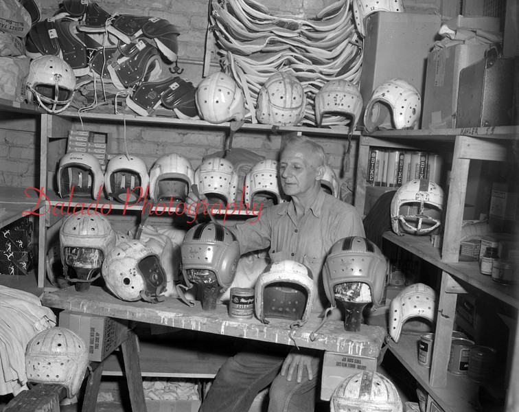 (August 1954) Adding a coal of paint to one of the many football helmets at the Lincoln School, where high school equipment is stored, is Daniel Carl.