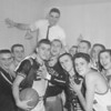 (Feb. 1960) Howie Landa, victorious Shamokin High School coach, is perched at the top of his team after the team threw him underneath the showers after the Greyhounds win.