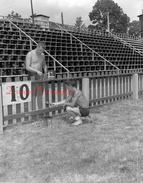 (Aug. 1955) Painting up the woodwork in Kemp Memorial Stadium is also a part of the summer maintenance program. Shown is Gary Rumberger, left, and Richard Dapra.