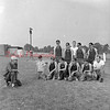 (08.01.1957) St. Mary's baseball team of Kulpmont listen to Coach Bill Madera. Also pictured, from left, G. Mekulski, F. Lentini, J. Gyursco, R. Mirarchi, P. Posca and G. Ladika, assistant coach; second row, B. Saiveikis, D. Molinar, d. D'Alexander and B. Mekulski