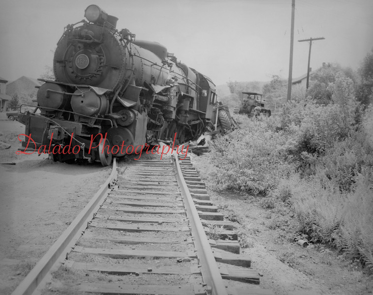 (06.27.1953) The locomotive of a 10-car Pa. Railroad coal and freight train is shown derailed at the Excelsior crossing on June 27, 1952, after striking a carryall being pulled by a bulldozer. The carryalll was wrecked and the tender and the first car of the train left the tracks, in addition to the locomotive. However, the operator of the bulldozer jumped from his machine and no one was injured.