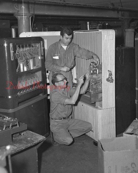 (10.06.55) Weller Brothers employees work on a cigarette machine. Pictured are Kimber Savidge, standing, who is assisting Charles Reed.