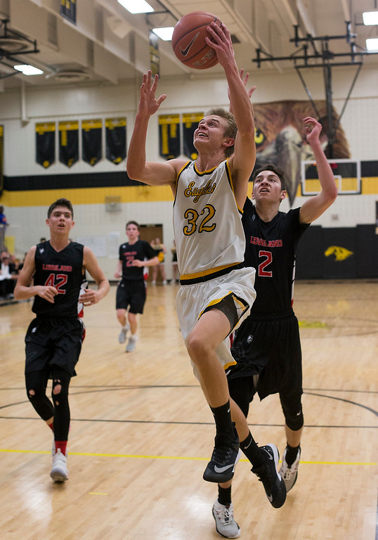 . Thompson Valley\'s Darren Edwards (32) gets past the defense of Loveland\'s Avery Rembao (2) for a shot Saturday evening Jan., 13, 2018 at Thompson Valley High School in Loveland. The Eagles beat the Indians 69-50. (Photo by Michael Brian/Loveland Reporter-Herald)