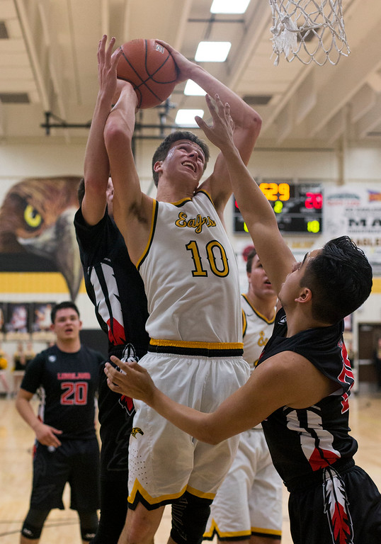. Thompson Valley\'s Justin Wiersema (10) fights for a basket against the Loveland defense Saturday evening Jan., 13, 2018 at Thompson Valley High School in Loveland. Wiersema added 32 points as the Eagles beat the Indians 69-50. (Photo by Michael Brian/Loveland Reporter-Herald)