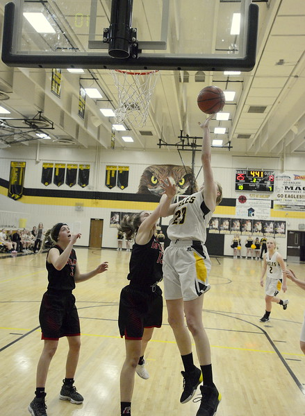 Thompson Valley's Dydnee Durtsche goes over Loveland's Claira Gilchrist for a basket during Saturday's crosstown game at the TVHS gym. Durtsche led the Eagles with 15 points in their 58-54 win.