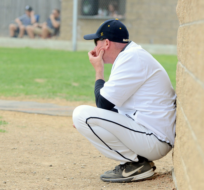 . Thompson Valley coach Jay Denning kneels in front of the dugout as he watches his team on the field in Saturday\'s game with Centaurus at Constantz Field. (Mike Brohard/Loveland Reporter-Herald)