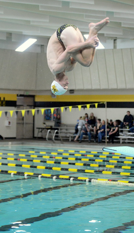 . Thompson Valley diver Logan Brian grabs his tuck during Thursday\'s Northern Conference dual with Longmont at the Dick Hewson Aquatic Center. (Mike Brohard/Loveland Reporter-Herald)