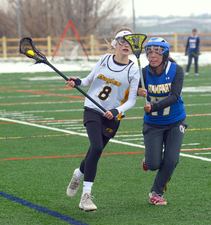 . Thompson Valley\'s Alex Brock pushes the ball up the field against the defense of Rampart\'s Makenzie Fontana during Saturday\'s game  at Loveland Sports Park. (Mike Brohard/Loveland Reporter-Herald)