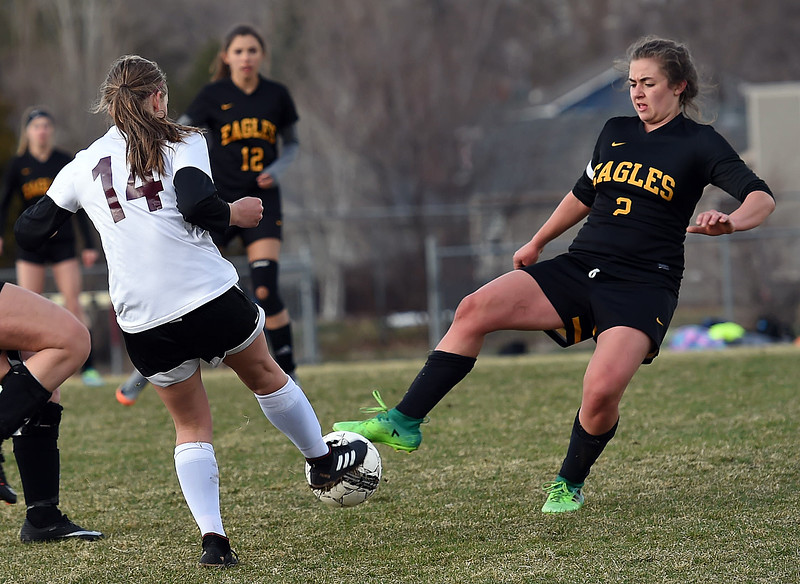 Thompson Valley's (2) Anna Mihaly and Berthoud's (14) Jessa Pirkey battle for control of the ball Thursday, March 29, 2018, during their game at Marr Field in Berthoud. (Photo by Jenny Sparks/Loveland Reporter-Herald)