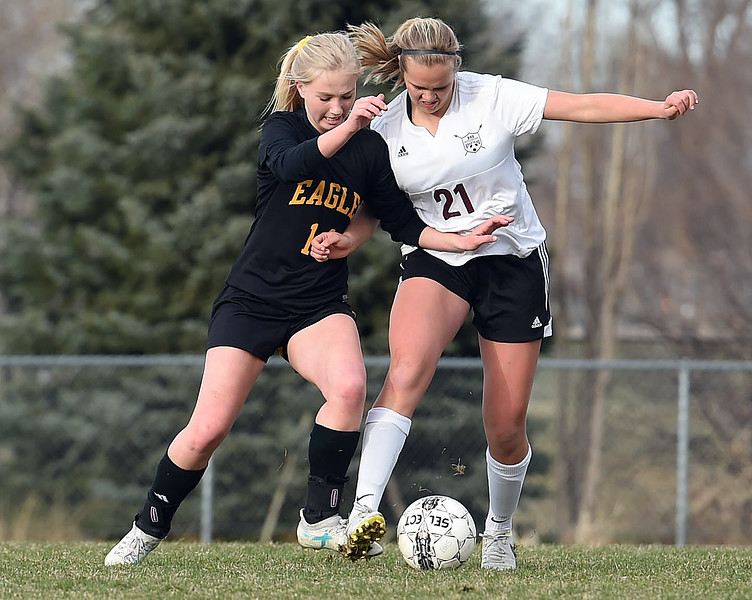 Thompson Valley's (14) Novi Briggs and Berthoud's (21) Dominique Rowell battle for control of the ball Thursday, March 29, 2018, during their game at Marr Field in Berthoud. (Photo by Jenny Sparks/Loveland Reporter-Herald)