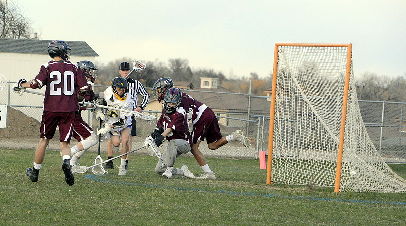 Thompson Valley's Greg Bilek weaves through a crowd of Cheyenne Mountain defenders to beat goalie Liam Hybl with a low shot in Monday's game at Patterson Stadium. The Eagles won 13-12. (Mike Brohard/Loveland Reporter-Herald).