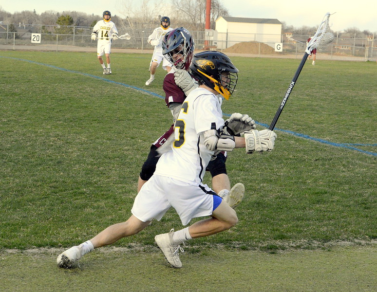 Cheyenne Mountain's August Johnson whacks Thompson Valley's Greg Bilek in the back with his stick as Bilek was on the attack in Monday's game. Bilek netted the game winner in the Eagles' 13-12 victory. (Mike Brohard/Loveland Reporter-Herald).