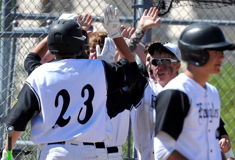 Thompson Valley players congratulate Aiden Schultz (23) after scoring a run Saturday at Denver North High School. (Cris Tiller / Loveland Reporter-Herald)