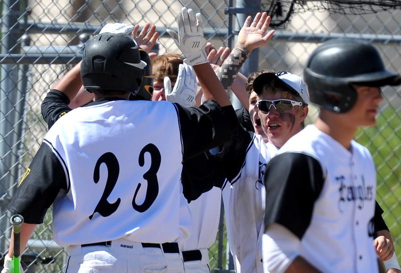 Thompson Valley players congratulate Aiden Schultz (23) after scoring a run Saturday at Denver North High School. (Cris Tiller / Loveland Reporter-Herald)