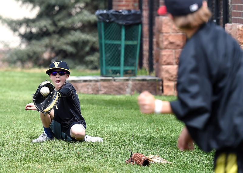 Cameron Denning, 8, catches a ball thrown by his pal Evan Raabe, 9, Monday, May 22, 2017, between innings during the Thompson Valley vs Golden state playoff baseball game at All Star Stadium in Lakewood. Cameron is the son of TVHS head coach Jay Denning and Evan's dad is the TVHS pitching coach. (Photo by Jenny Sparks/Loveland Reporter-Herald)