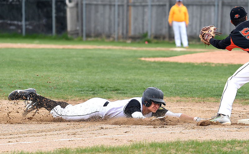 Thompson Valley's #4 Cameron Nellor slides safely in to third base as Greeley Central's #5 Raul Morales tries to catch the ball during their game Wednesday, April 26, 2017, at Constantz Field in Loveland. (Photo by Jenny Sparks/Loveland Reporter-Herald)