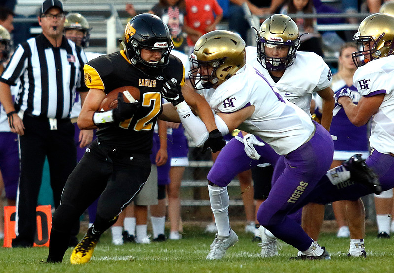 Thompson Valley's Kobi Turner (12) pushes past Holy Family's Brandon Biehler (15) to gain yards on Thurdsay, Sept. 21, 2017 at Patterson field. (Photo by Lauren Cordova/Loveland Reporter-Herland)